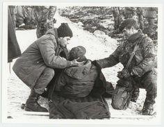 En cuclillas el Granadero VGM Miguel Angel Piaggio, ayudando a un camarada herido, en Monte Harriet.