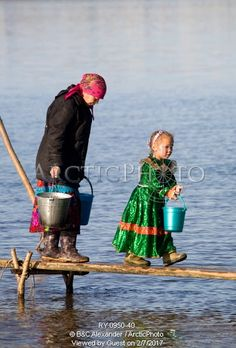Image of lidiya tokhma, a khanty woman, collecting water with her grandaughter, alona, at a fishing camp on the river ob near aksarka. yamal, western siberia, russia by ArcticPhoto