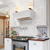 The cooking zone is elevated by a mantel, sconces, and dentil and crown molding. For a low-cost upgrade, subway tile over the range was angled and framed to create an inset. Oversize porcelain floor tile was laid diagonally to visually enlarge the space.   Utensil rack: IKEA. Range: Frigidaire