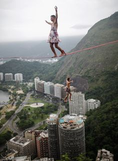 Río de Janeiro, Brazil - Participants balance on a tightrope between two boulders in the Cantagalo favela during the Highgirls festival. The event centers on women and only allows men to participate if they are wearing girl's clothing.
