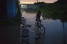 A girl rides her bike through a flooded street in the Parque Sao Bento shanty town of Rio de Janeiro, Brazil