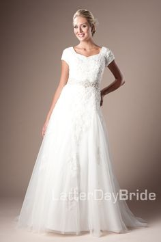 Mariza - This is sure to be one of our most classic modest wedding dresses. It features beaded lace appliques sewn onto Open-weave French Tulle over layers of organza and satin, accented with a beautiful Swarovski crystal beaded band and rounded square neckline. Gown pictured in ivory/ivory/champagne. $1590.00