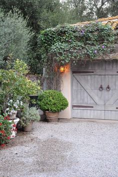 Container gardening borders drive, overhang above garage doors, hardware on…