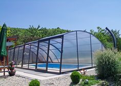 Retractable swimming pool enclosure RAVENA in the nice and clean garden.