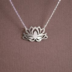 Blooming beautifully and cleanly on the surface of murky waters, the lotus flower is known as a symbol of rebirth, purity, spiritual awakening, and enlightenment.  This design was handcut from a sheet of sterling silver using a jewelers saw. It measures 9/16 x 1 1/16 (1.43cm x 2.70cm) and is 0.66mm thick. This pendant will hang from a sterling silver necklace of your length choice that closes with a sterling silver lobster clasp.  All of our jewelry comes in a gift box ready for giving.