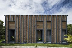 vilela florez arranges bamboo in a herringbone pattern for the facade of this brazilian residence