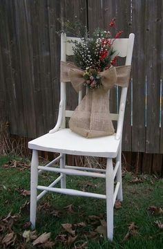 Chair decorated for Christmas with burlap ribbon, springs and berries (porch)
