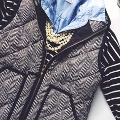 Navy and white striped shirt layered over a button down chambray shirt, with pearls and a tweed vest