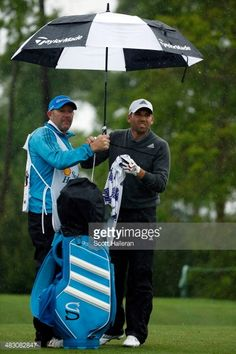 News Photo : Sergio Garcia of Spain stands with an umbrella on...