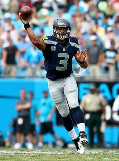 Russell Wilson #3 of the Seattle Seahawks drops back to pass against the Carolina Panthers during their game at Bank of America Stadium on September 8, 2013 in Charlotte, North Carolina.