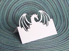 """Looking for the perfect Medieval, Fantasy or Fairytale themed table place card? This unique dragon silhouette place card is perfect for table numbers or names for your wedding or party. Add this dragon place card to my dragon invitation wedding set to create your dream Medieval, Renaissance, or Fantasy Fairytale wedding! This original design is created with cut paper, using acid free white linen card stock. It measures 3.75"""" x 2.75"""" when folded. It is shipped in a protective envelope, inside…"""