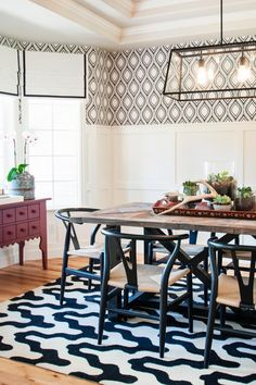 This stunning dining room is anchored by a farmhouse table and chairs reminiscent of midcentury modern design. Black and white wallpaper and a rug are the can't-be-missed design elements in the room, and the color scheme is echoed in the window treatment, light fixture and chairs. Botanicals and antler horns bring nature indoors, and the red tray and table add a punch of color.