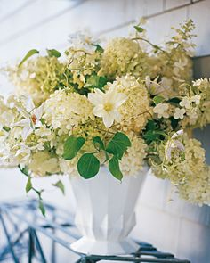 Cotton-Garden Arrangement-  This display showcases the unrestrained beauty of hydrangeas. An armful of the flowers overflows a generous glazed-iron urn-shaped vase in an effortlessly elegant way. Tendrils of clematis winding through the blooms emphasize the cottage-garden feeling