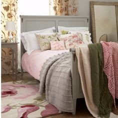Pile a beautiful painted bed with vintage floral cushions. The bright raspberry and green tones are echoed by the bold rug and more subtly in the tulip design curtains.