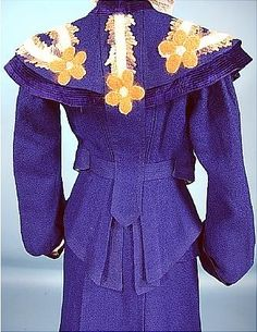 "Circa 1904 Rare and Beautiful ""Military Style"" Tailored Royal Blue Wool, Angora and Velvet 2-piece Trained Walking Suit.  The jacket has a peplum attached!  There are no closures on the jacket front, just the interior. waistband holds it closed.  The lapels and large collar are embroidered in a floral design with ribbons and angora in lavendar-grey, off-white, light green and ""maize-color"", trimmed with deep top-stitched navy velvet. Detail of back."
