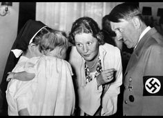 A picture dated 1939 shows German Nazi Chancellor and dictator Adolf Hitler with his companion Eva Braun talking to a baby held by a nun. AFP/Getty Images
