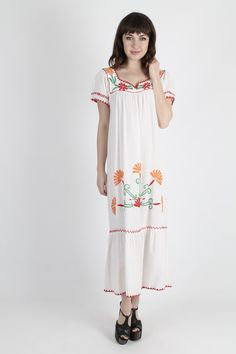 Vintage 70s ethnic India boho maxi dress.  Tailored chest with fluttery cap sleeves.  Gathered and draped skirt with ruffle trim.  White rayon with bright floral embroidery.     size estimate: S/M shoulders: 13 bust: 36 waist: - hips: 45 total length: 49     Model is 59 and measures 32 bust, 24 waist, 35 hips Belts and other accessories are not included.