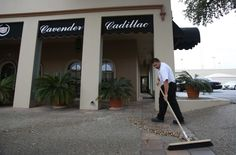 Anthony Galindo sweeps leaves outside of Cavender Cadillac, at 801 Broadway, on Friday March 8, 2013.  The location will shut down once the dealership moves to a new location at Loop 1604 and Lookout Road next summer.