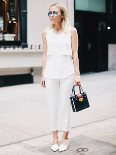 An all-white look is paired with pointed-toe loafers and a black box bag