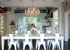 crystal chandelier with farm table and industrial chairs