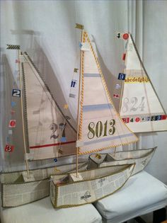 Vintage ledger paper boats. Made out of poster board covered with ledger paper, washi tape, and stamped numbers.  Via Candice Dolan.