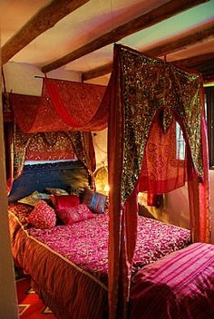 Ethnic feel four poster bed, with lavish fabric drapes in warm sultry colours, plenty of colour contrast to give it the extra edge