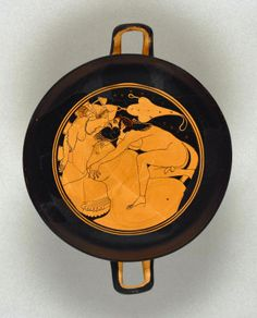 Attic Red-Figure Kylix. Date: about 500 - 490 B.C. Interior: a wreathed satyr clambers over a large rock in order to kiss a sleeping maenad, who is reclining on a striped cushion. In the background, above her head, is a wineskin, inscribed KALOS. HO PAIS KALOS written in the background.