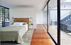 O estilo brutalista entra através das paredes de vidro no quarto projetado pela arquiteta Adriana Rolim. Como a estrela é a arquitetura, o interior é neutro