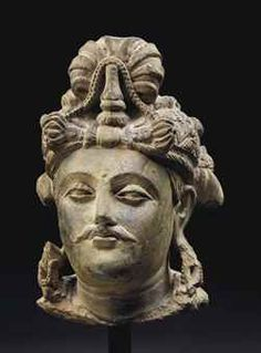 TETE DE BODHISATTVA EN SCHISTE GRIS REGION DU GANDHARA, IIEME-IIIEME SIECLE The head is carved with a serene facial expression with downcast lidded eyes below arched eyebrows and a raised urna. His mouth is framed by a moustache. His hair is combed in a chignon and secured with a crown decorated with a central ornament. 8 5/8 in. (22 cm.) high, stand