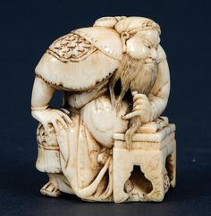An ivory netsuke. Mid-19th century, signed Tomotane. A very good study of Kwanju reading at a low table. All the details lightly worn with a good patina. Illustrated Neil Davey. Hindson collection. Lot 438. Old English collection. Height 4.7 cm