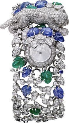 CARTIER. High Jewellery panther décor secret watch, quartz movement. Rhodium-finish white gold case and bracelet set with 12 leaf-shaped engraved sapphires totaling 11.89cts, 8 leaf-shaped engraved emeralds totaling 5.54cts, 1 sapphire and 1,212 brilliant-cut diamonds totaling 14.60cts, emerald eyes, onyx, silvered brushed sunray effect dial, diamond marker at 12 o'clock, rhodium-finish 18K yellow gold sword-shaped hands. Water-resistant to 3 bar (approx. 30 metres). Unique piece.