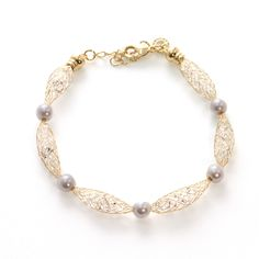 """The wire cocoon encloses elegant clear stones and adds even more femininity with delicate pearl accents. This adjustable bracelet is great to stack or wear as is! Length: 7"""" #MORANA"""