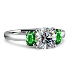 Two perfectly matched oval cut diamonds flank the center stone of your choice…this is the symmetrical appeal of Brilliance's Oval Emerald Ge...
