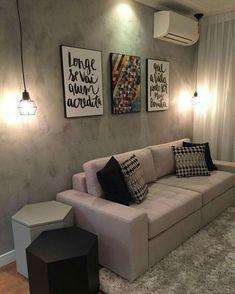 Sala simples em tons de cinza e preto com quadros coloridos