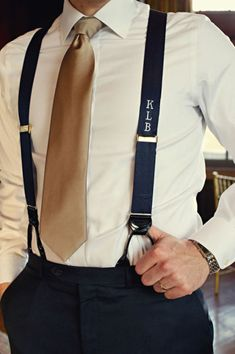 This groom looks like a million bucks in his gold tie and suspenders