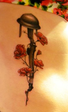 Beautiful military tribute tattoo. A helmet resting atop a pistol, all wrapped in pretty flowers. Nice message.