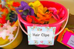 "girl birthday luau - had bright sand buckets full of flower hair clips, leis and ""grass"" mini-skirts for all the girls at the door"