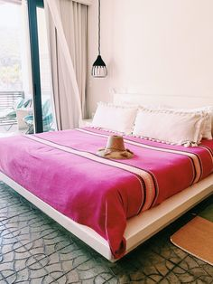 pink mexican blanket on bed at hotel san cristóbal.