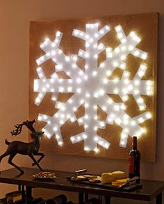 They used a drop cloth as a canvas, masked off a snowflake with painters tape, and then sprayed it with gold spray paint. Then they poked some holes and put Christmas lights through them. Pretty darn gorgeous if you ask me.