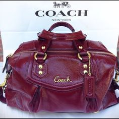 Coach purse  Really pretty red with pink interior. Used a couple of times but then was sitting in my closet for awhile. Upon close inspection it has a few stains (yellowish) in the corners *see third pic*, & inner pockets but I dabbed it clean with soap and water and that seemed to diminish it a bit. Other than that it's in pretty good condition. Length 12 in. Width 5 in. Coach Bags Satchels