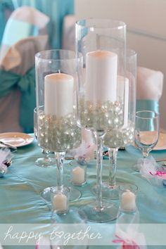 Tall 'wine glass' holders with clear marbles and pillar candles = non-traditional centerpieces