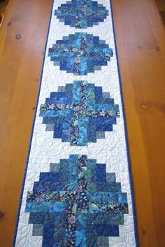 Using the lob cabin block I used blue fabrics for the center with narrower strips for the white fabric so the blocks appear as circles. This table runner has stunning colors. A couple of the fabrics h