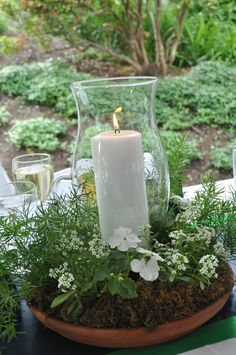 Center Pieces -- Large terracotta base with a smaller base upside down in the middle as the base for the hurricane glass.  Use any flowers you like