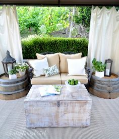patio decor - I like the half-barrels turned side tables, and the hanging curtains