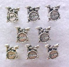 "Drums Decorative Push Pins.  Perfect for your favorite Drummer. Silvertone metal cast with great detail. Code 6721.  Approx. 3/4"".  $8.95.  URL  http://www.pushpinsandfabriccorkboards.com/drums-tibet-silver-decorative-push-pins.html"