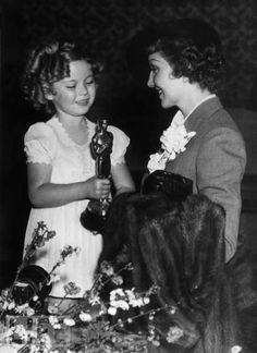 "Certain she would lose, New York-bound Colbert skips the 1935 Oscars. When she wins Best Actress for ""It Happened One Night,"" she's summoned from the train station to the banquet, where Temple hands her the trophy."