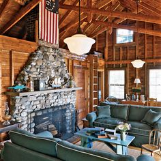 Family Room with a large stone fireplace, wooden walls and high, exposed beams