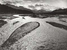 1947 Teklanika River, Mount McKinley National Park, Alaska [shallow rippling water, sandbars; high horizon with mountains, clouds] by Ansel Adams 84.93.23