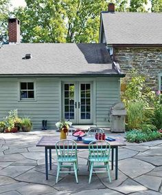 A broken-bluestone patio, decked out with a pro-style stainless-steel grill and table seating, lies just beyond the kitchen's French doors.