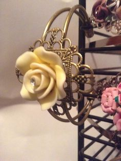 Bronze filigree bangle bracelet with a 25mm yellow polymer clay rose and centered with a clear gem.